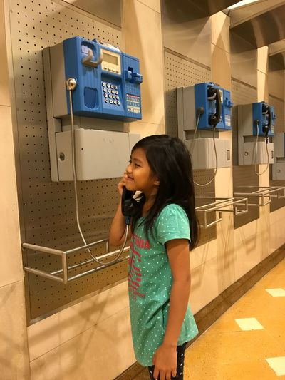 Girl using pay phone
