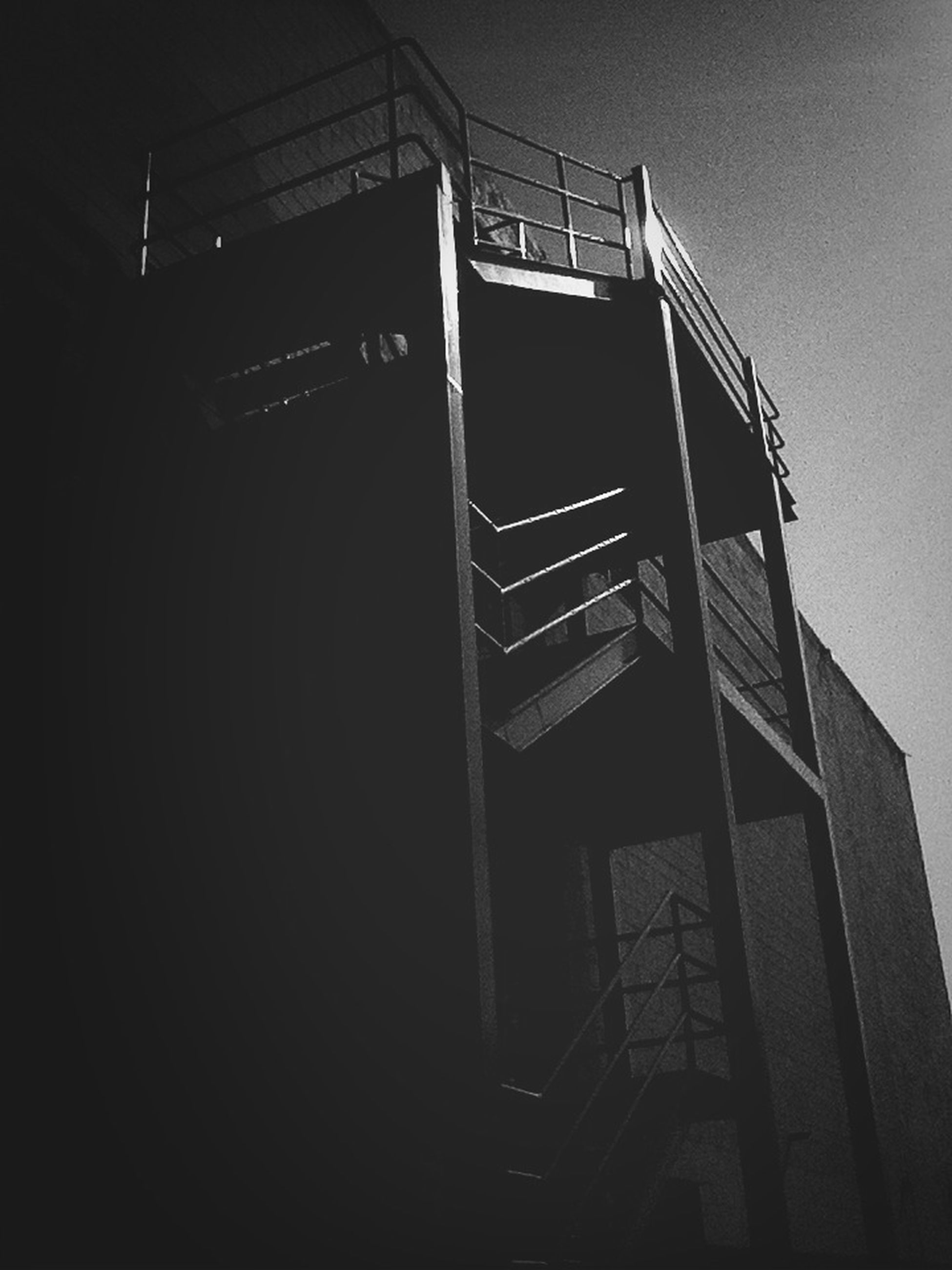 low angle view, built structure, technology, dark, architecture, old-fashioned, old, no people, copy space, building exterior, sky, abandoned, night, outdoors, silhouette, clear sky, obsolete, building, metal
