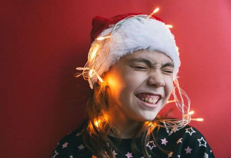 Cute little girl in Santa Claus hat Burning Celebration Christmas Colored Background Eyes Closed  Fire Flame Front View Hair Hairstyle Hat Headshot Holiday Indoors  Leisure Activity Mouth Open One Person Portrait Red Young Adult