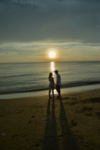 Silhouette Couple At Beach Against Sky During Sunset
