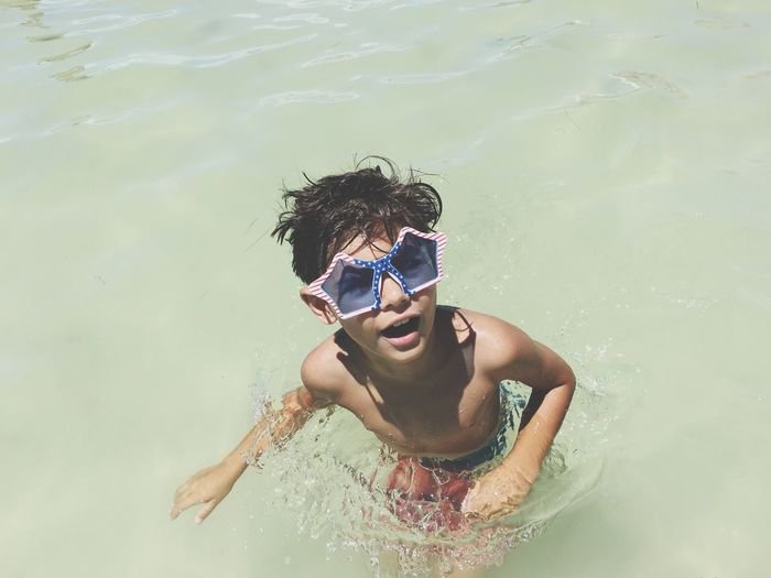High Angle View Of Shirtless Boy Wearing Sunglasses In Sea On Sunny Day
