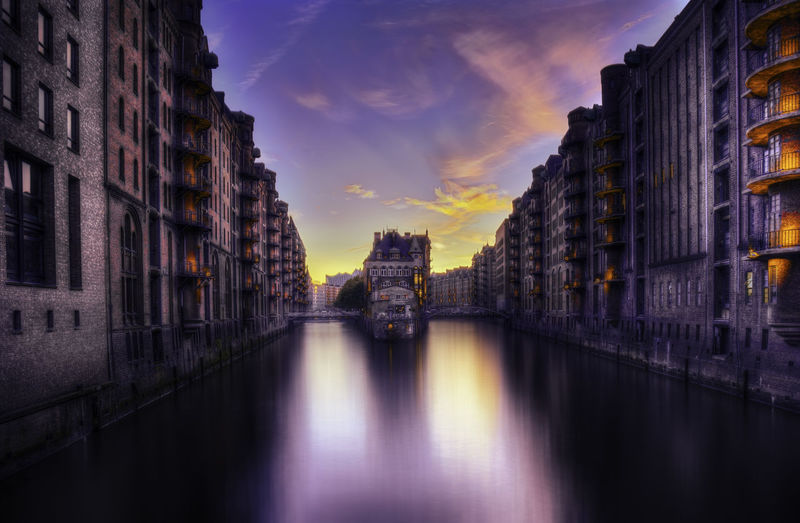 Buildings on canal at sunset