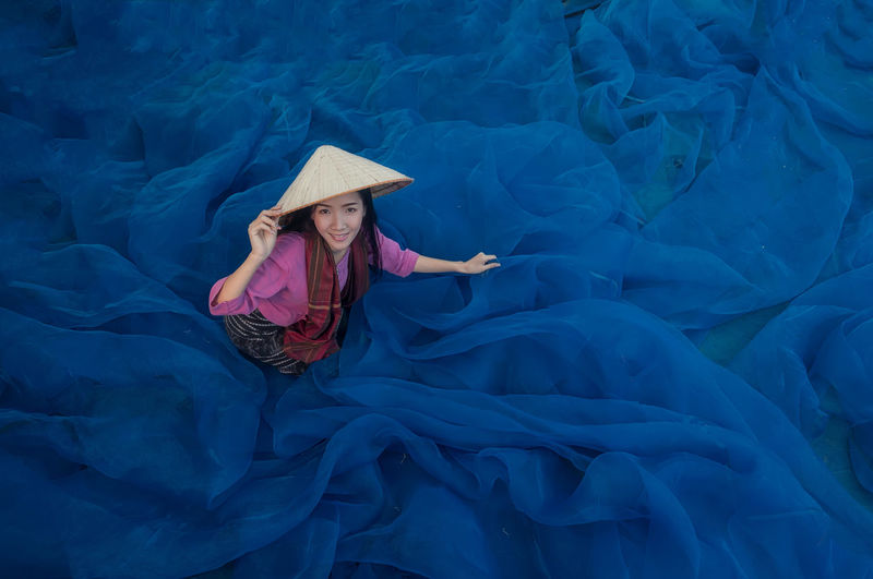 Beautiful woman fisherman is repairing fishing nets, Fisherman is cleaning Thai fishing nets,Thailand Adult Beautiful Woman Blue Clothing Front View Full Length Hat Indoors  Leisure Activity Lifestyles Lying Down One Person Portrait Real People Smiling Textile Women Young Adult Young Women