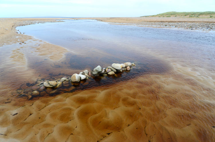 Partial dam Flowing Water Beach Brown Outdoors Pile Of Stones Sand Sea Water