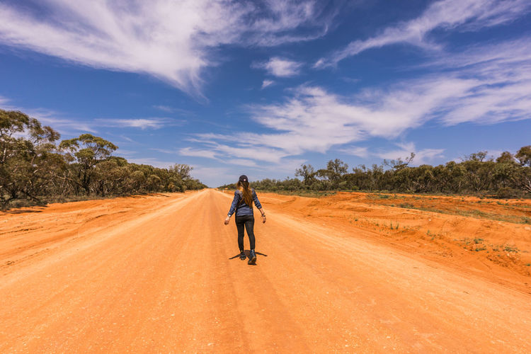 Rear view of woman walking on dirt road against sky