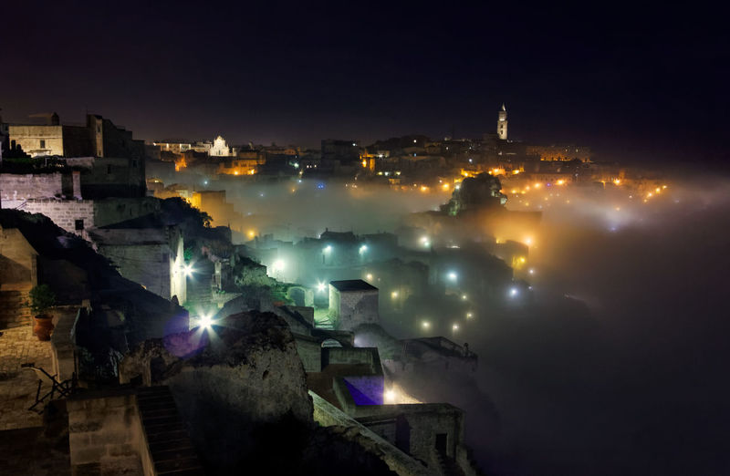 Fog in the Sasso Caveoso City Silhouette Fog In An Ancient Cit Historical City In The Fog Matera At Night Nighttime Lights In The Old Houses At Sasso Caveoso In Matera Sasso Caveoso In The Fog