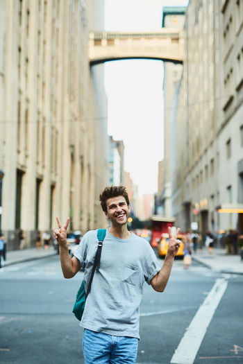 Young man gesturing peace sign while standing in city