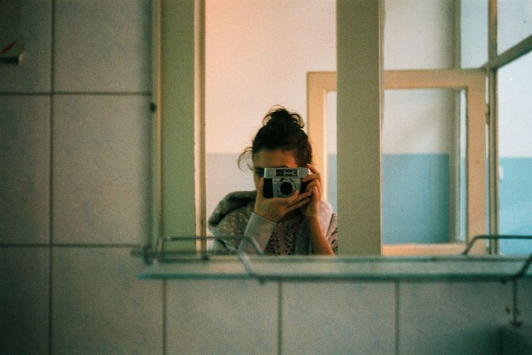 Woman Taking Selfie Through Camera Reflecting On Mirror At Home