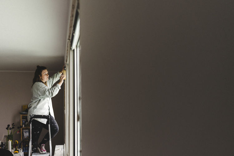 Midsection of woman standing against wall at home