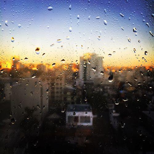 Buildings against sky seen through wet glass window at dusk