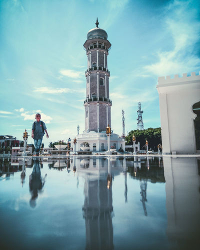 Reflection of man and building in puddle against sky