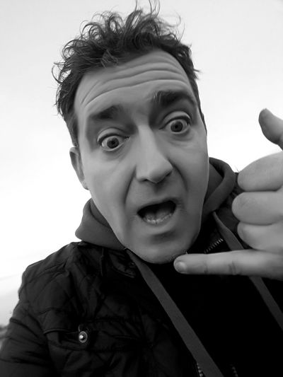 Low angle view of shocked man showing hand sign