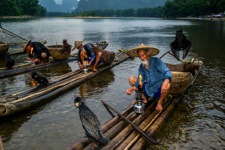Men With Birds On Wooden Rafts In Lake