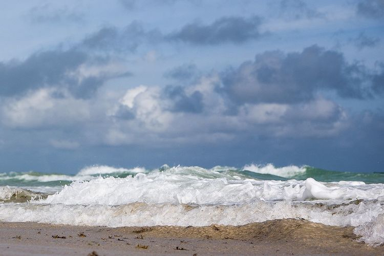 Waves in sea on shore at beach against sky