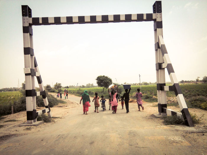 People Teamwork Large Group Of People Day Sky Outdoors Adult Children Rural Scene Rural Life Walking India Nature Road Railway Crossing Gates Back View Women Women And Children