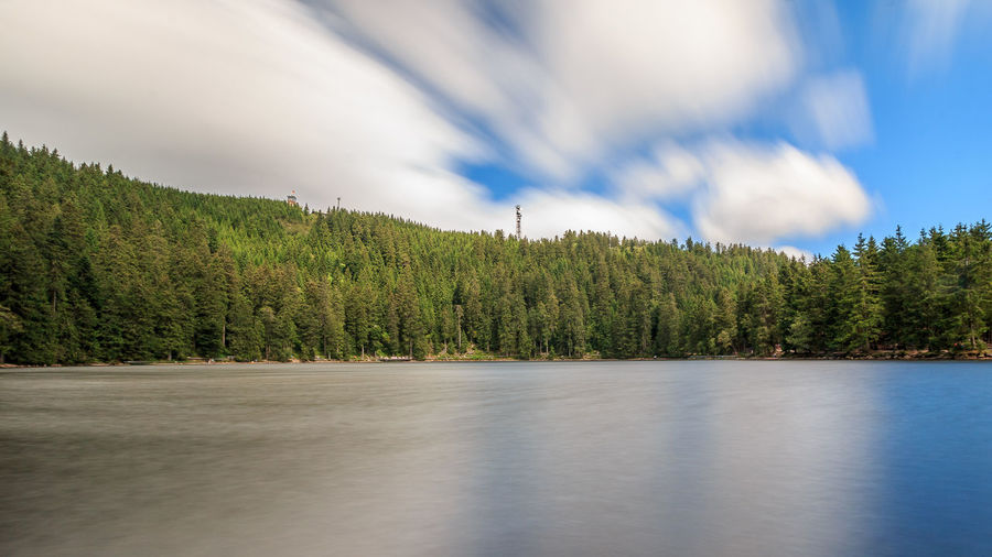 Lake with trees against cloudy sky