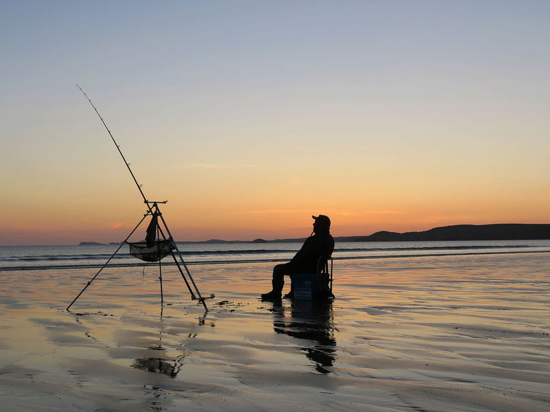 Beach Photography Calmness Newgale Pembrokeshire Coast National Park Sunset Silhouettes Fisherman Fishing Fishing Equipment Men Nature Orange Color Pembrokeshire Coast People Real People Sea Sky Sunset Tranquil Scene Tranquility