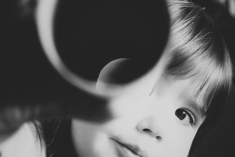 Close-up of cute toddler playing with cylindrical object