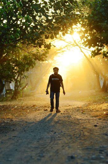 Full length of silhouette man standing on street during sunset
