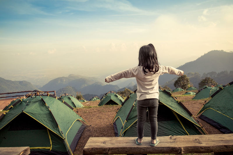 Rear view of girl with arms outstretched standing on retaining wall against sky at campsite