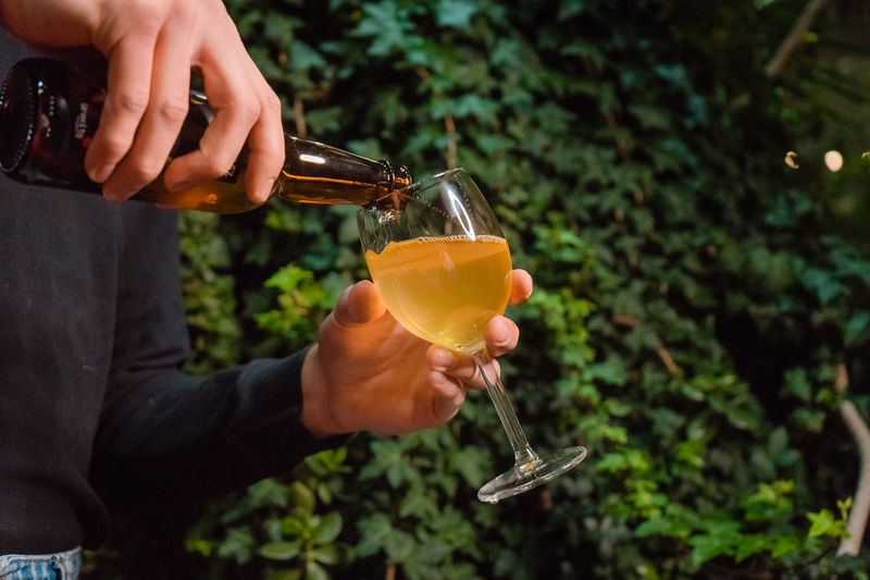 A waiter pours cider into a glass against the background of greenery.