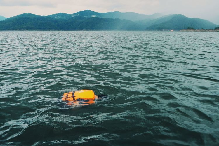 High Angle View Of Man Swimming In Sea Against Mountains