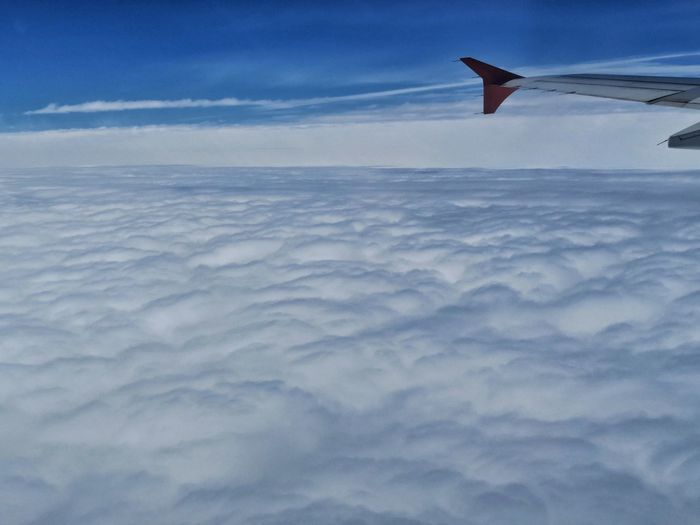 Close-up of airplane wing over cloudscape