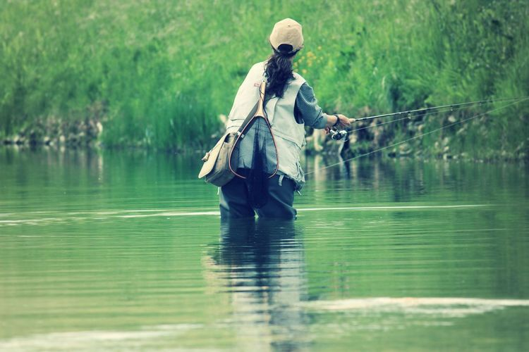 Rear view of woman fishing in river