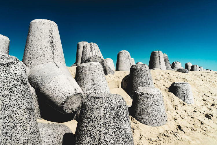 Architecture Beach Blue Built Structure Clear Sky Concrete Day Land Low Angle View Nature No People Outdoors Ruined Sand Sky Solid Sunlight Sunny Tetrapod