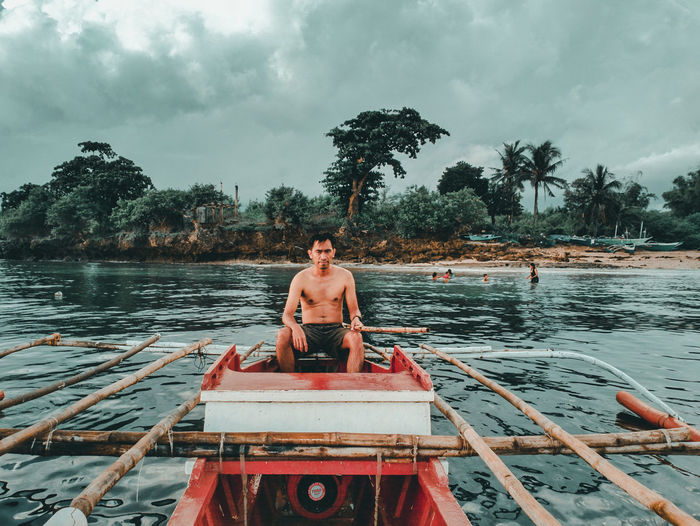 Portrait of shirtless man sitting on boat in river against sky