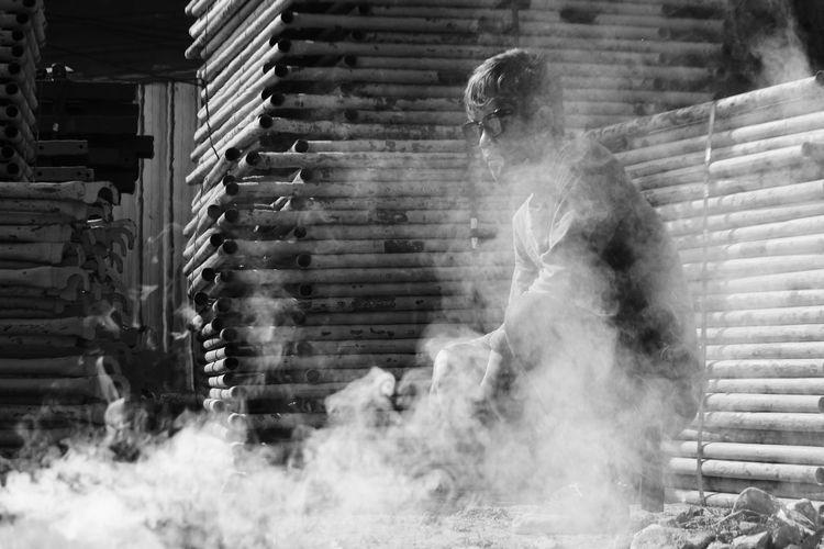 Young man wearing sunglasses while crouching amidst smoke