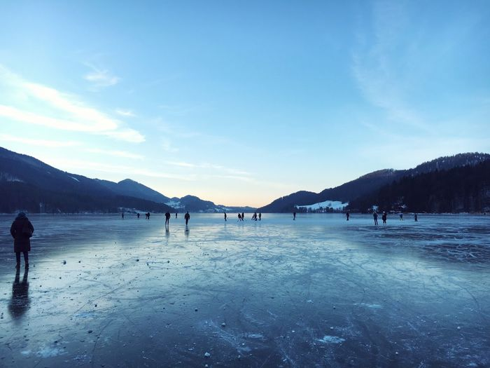 People walking on frozen water against sky during sunset