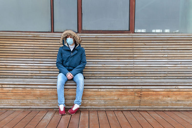 Full length of man wearing mask while sitting on bench