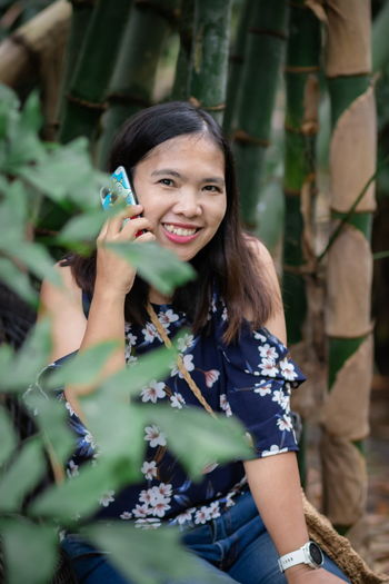 Portrait of smiling woman sitting by plants