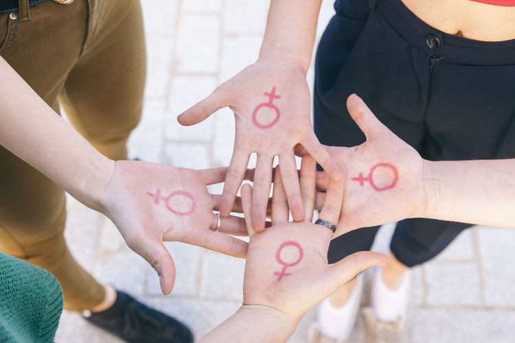 High angle view of friends showing pattern on hand