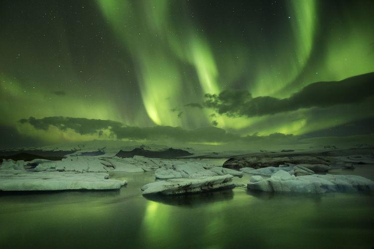Reflection Of Aurora Polaris On Frozen Sea Against Sky