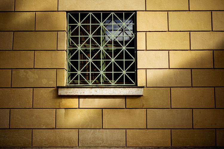Low angle view of window on brick wall