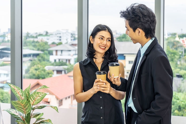Young couple standing against window