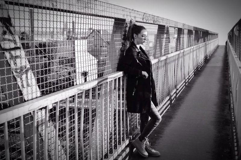 Reflection of man on railing in bridge
