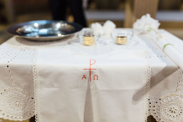Table Indoors  No People Still Life Text White Color Communication Close-up Textile Focus On Foreground Glass Event Setting Baptism Baptism Day Religion Religion And Beliefs Religious Traditions Catholicism Catholic