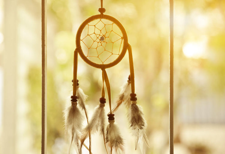 Close-up of dreamcatcher hanging at window against blurred background