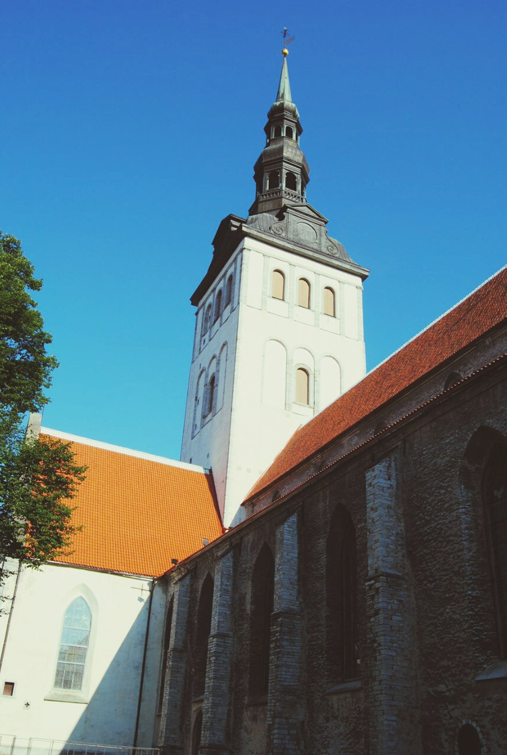 building exterior, architecture, built structure, low angle view, clear sky, blue, church, place of worship, religion, window, tower, tree, sunlight, residential structure, residential building, house, day, building, high section