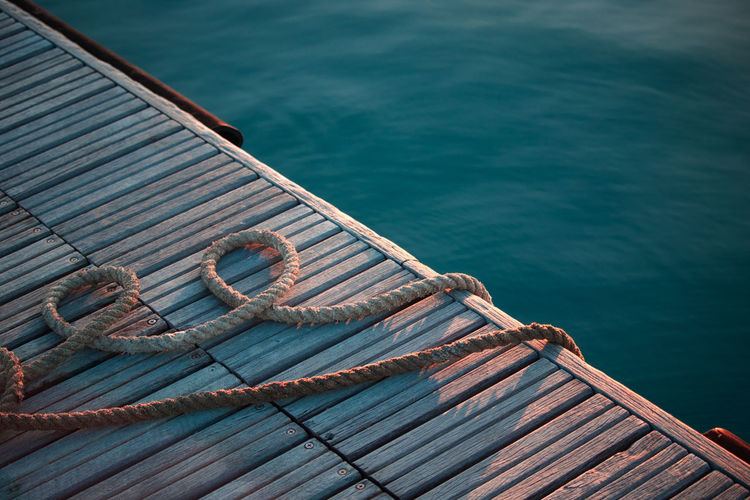 High angle view of rope on pier over sea during sunset