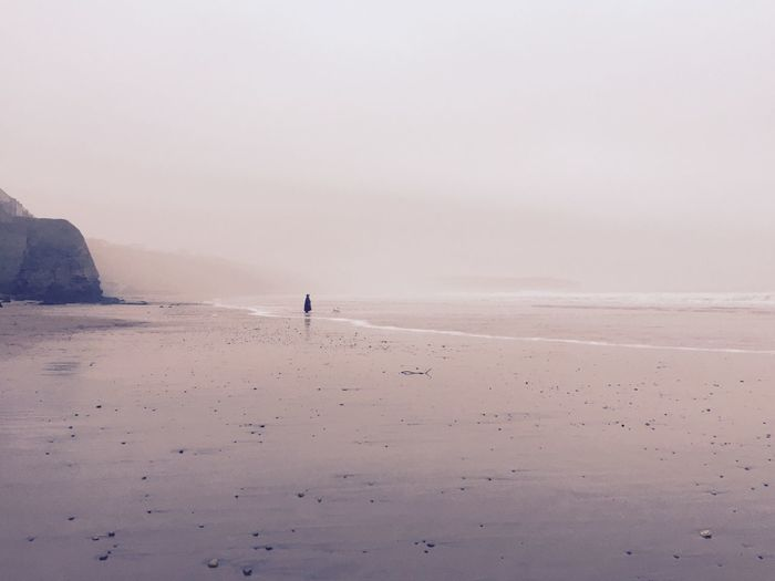 Woman standing at distant on foggy beach