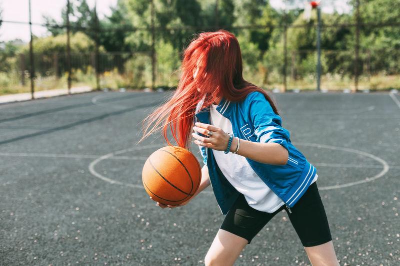A beautiful teenage girl leads a basketball on a sports field, a girl learns to play basketball
