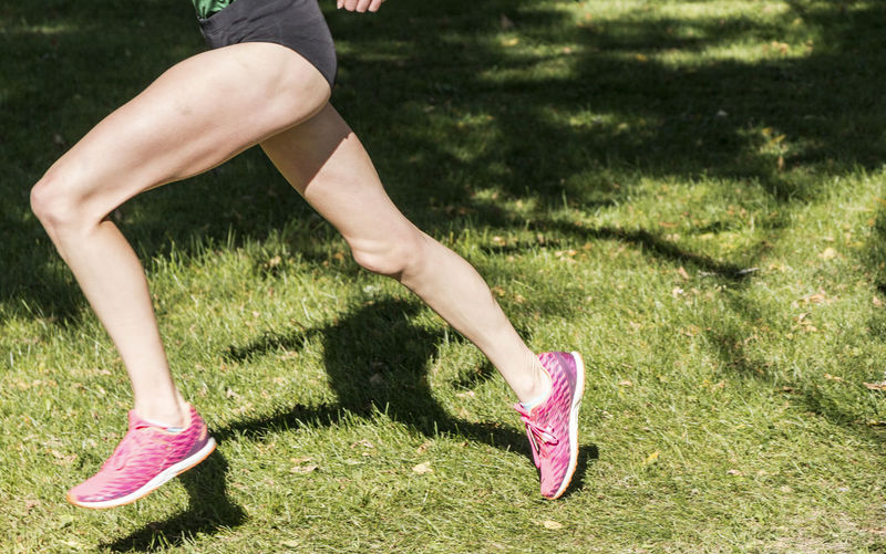 Low section of woman wearing pink shoes running on grass