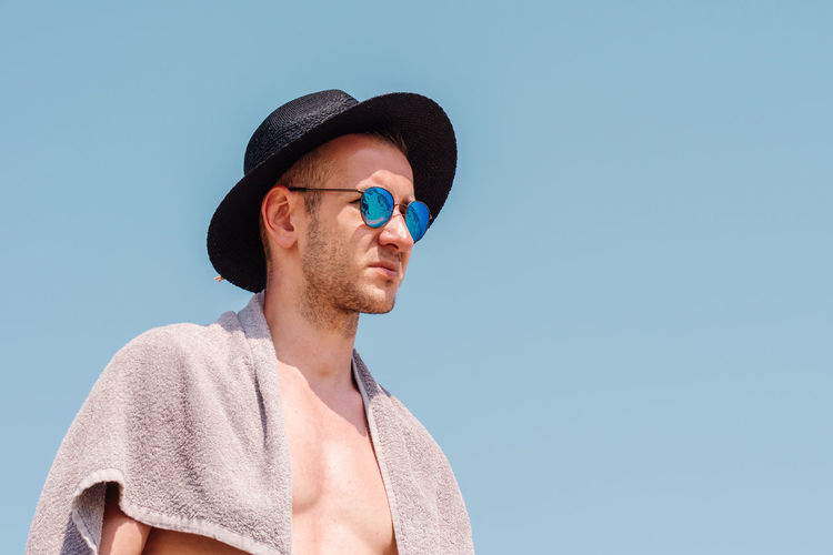 Man Wearing Sunglasses And Hat Against Clear Blue Sky