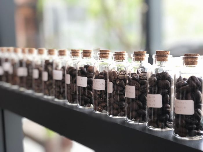 Close-up of roasted coffee beans in glass bottles on shelf