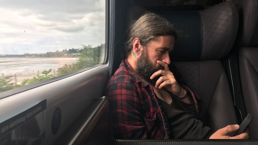 Thoughtful man using mobile phone while sitting in train