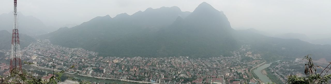 mountain, architecture, mountain range, outdoors, day, built structure, city, fog, landscape, building exterior, nature, no people, sky
